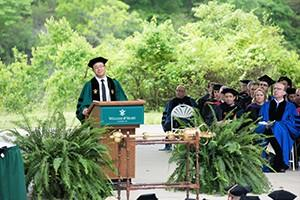 A man speaks from a podium during commencement. Faculty members are seated behind him, listening to the speech.