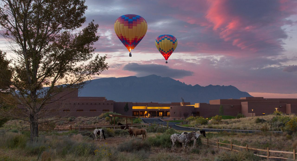 Balloons floating over academic building at sunset. A few horses are in the foreground.