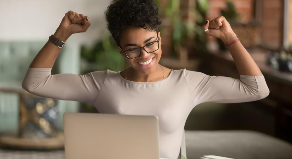Person with arms raised in victory at laptop
